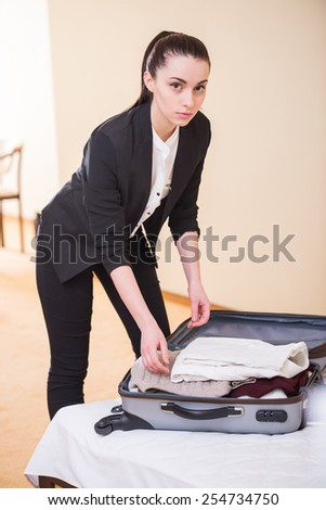 Happy business woman is packing things in suitcase in hotel room. - stock photo