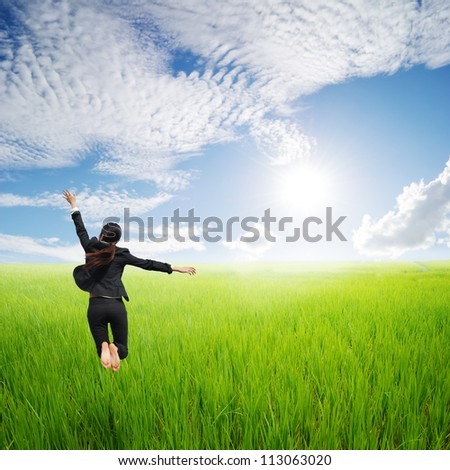 Happy business woman jumping in green rice field and clouds sky