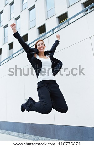 Happy business woman jumping into the air in front of office building - stock photo