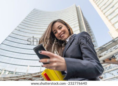 happy business woman looking at her phone and smiles - stock photo