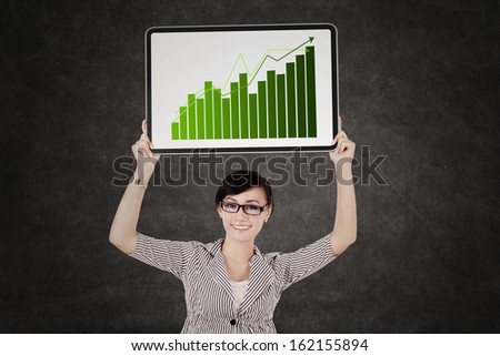 Happy business woman showing growth graph over her head - stock photo