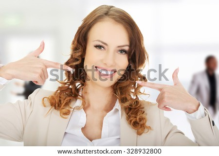 Happy business woman shows us her teeth. - stock photo