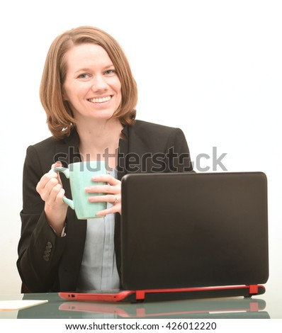 Happy business woman sitting at desk with coffee smiling at work - stock photo