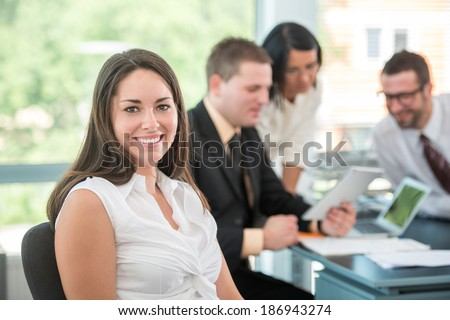 Happy business woman sitting in modern office - stock photo