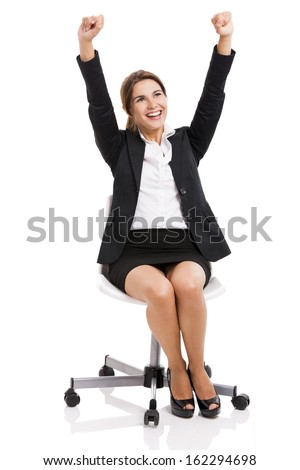 Happy business woman sitting on chair with arms up, isolated over white background - stock photo