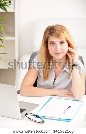 happy business woman sitting, thinking and working on laptop computer at office - stock photo