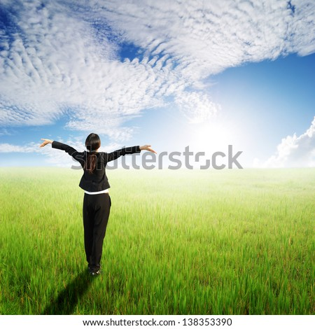 Happy Business woman standing to clouds sky in grassland
