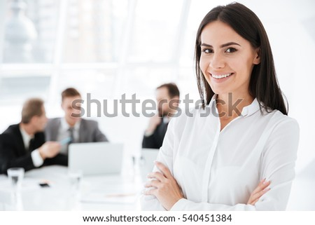 Happy Business woman standing with arms crossed with colleagues on background