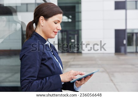 Happy business woman typing on tablet PC in front of her office in the city