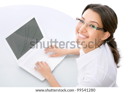 Happy business woman using a laptop. Looking at camera - stock photo