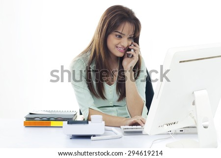 Happy business woman using cell phone and computer at office