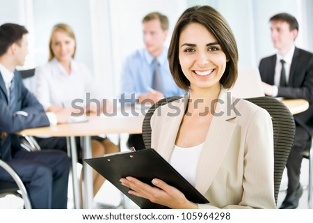 Happy business woman with colleagues at the back - stock photo