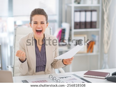 Happy business woman with document rejoicing - stock photo