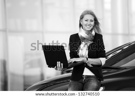 Happy business woman with laptop sitting on the car - stock photo