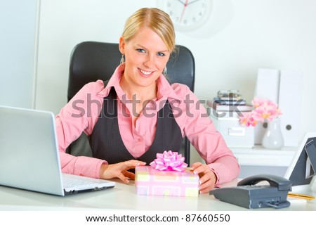 Happy business woman with present box at office desk - stock photo