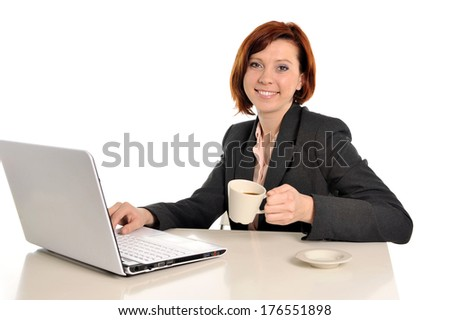 Happy business woman with red hair smiling at work writing on computer and drinking coffee isolated on white background