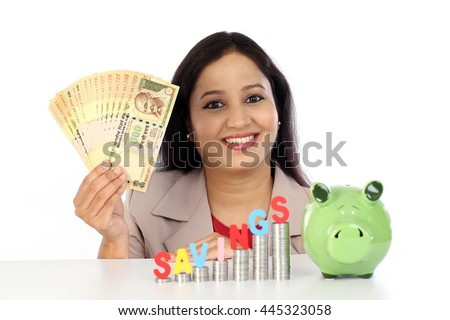 Happy business woman with stack of coins and holding rupee notes - stock photo