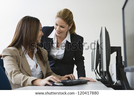 Happy business woman working on computer while colleague looking at her - stock photo