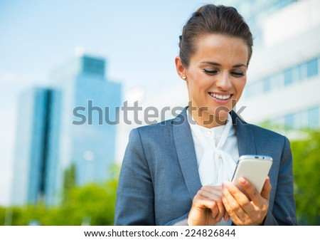 Happy business woman writing sms in office district - stock photo