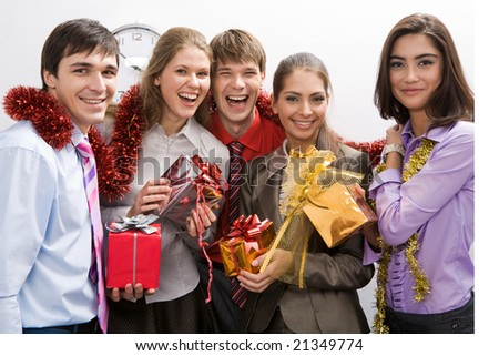 Happy businessgroup with colorful presents in hands looking at camera and smiling - stock photo