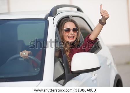 Happy businesslady in dark red shirt driving her car and showing thumb up. Smiling lady in sunglasses taking steering wheel of her new car. - stock photo