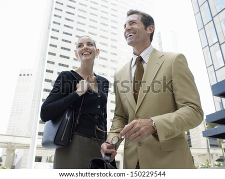 Happy businessman and businesswoman looking away against office building - stock photo