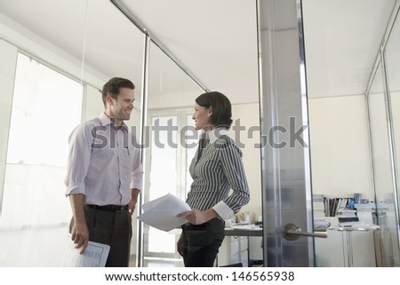 Happy businessman and businesswoman with paperwork taking in office - stock photo
