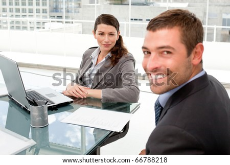 Happy businessman and businesswoman working together on a laptop during a meeting