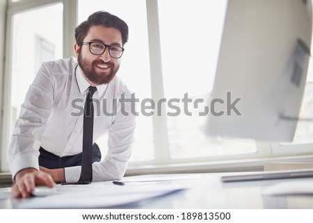 Happy businessman at workplace looking at camera in office - stock photo