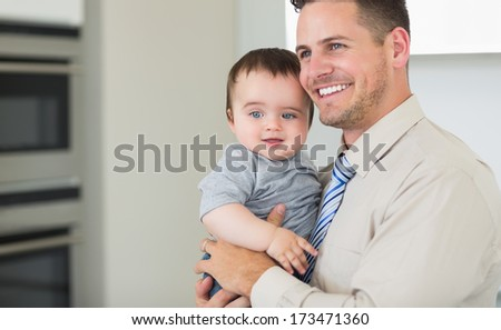 Happy businessman carrying baby boy at home - stock photo