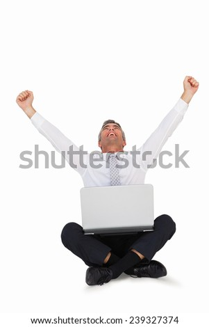 Happy businessman cheering and sitting with his laptop on white background - stock photo