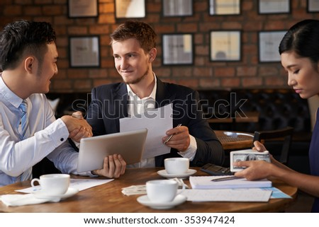 Happy businessman congratulating his colleague with successful deal - stock photo