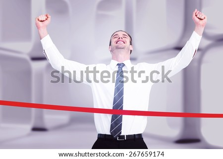 Happy businessman crossing the finish line against white abstract room - stock photo