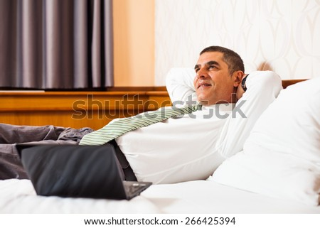 Happy businessman day dreaming in hotel room - stock photo
