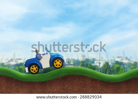 Happy businessman driving a toy car - stock photo