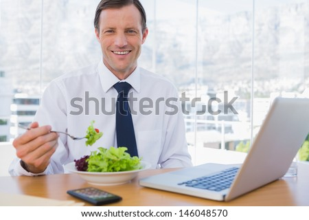 Happy businessman eating a salad on his desk during the lunch time - stock photo