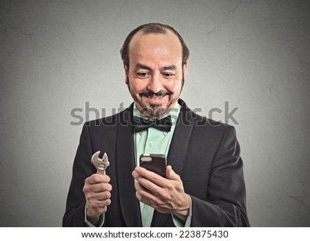 Happy businessman executive looking at smartphone holding wrench in hand isolated office grey wall background. Human face expression emotion feeling. Leadership tools, key to solve problem concept  - stock photo