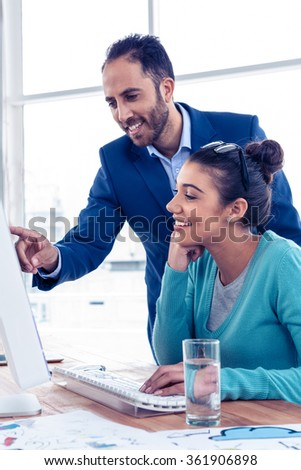 Happy businessman explaining to coworker over computer at creative office - stock photo