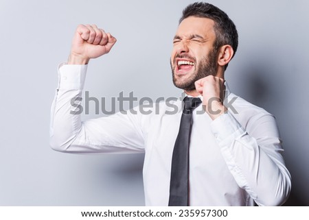 Happy businessman. Happy mature man in shirt and tie gesturing and shouting while standing against grey background - stock photo