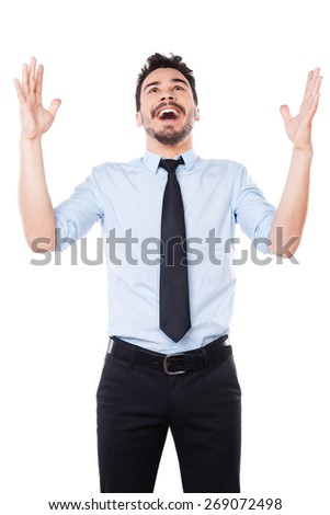 Happy businessman. Happy young man in shirt and tie keeping arms raised and smiling while standing against white background - stock photo