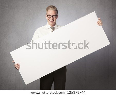 Happy businessman holding empty white panel with space for text isolated on grey background. - stock photo