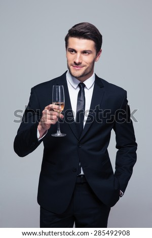 Happy businessman holding glass of champagne over gray background and looking away - stock photo