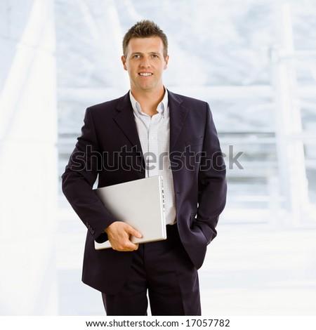 Happy businessman holding laptop computer indoor smiling - stock photo