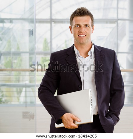 Happy businessman holding laptop computer indoor smiling. - stock photo