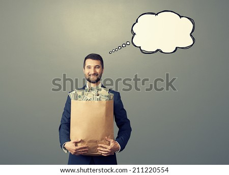 happy businessman holding money bag with drawing speech empty bubble over grey background - stock photo
