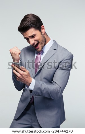 Happy businessman holding smartphone and celebrating his success over gray background - stock photo