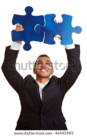 Happy businessman holding two blue jigsaw pieces