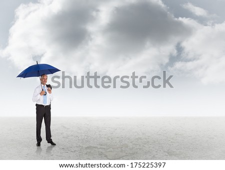 Happy businessman holding umbrella against cloudy sky background