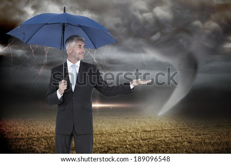 Happy businessman holding umbrella against stormy sky with tornado over field