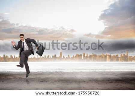 Happy businessman in a hury against large city on the horizon